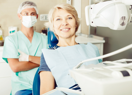 Portrait of smiling mature woman in dentist office waiting for dental procedure