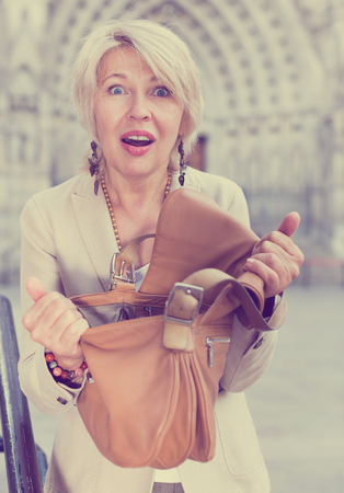 Mature woman is upset because her purse was been stole from bag on the street.