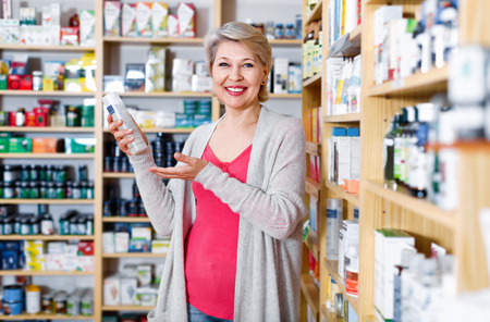 Smiling positive female customer looking for products of skin care in specialized shop