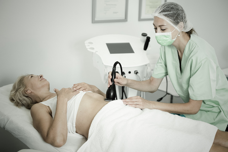 Beautician doing innovative procedure of cryoliposuction to female in cosmetic office