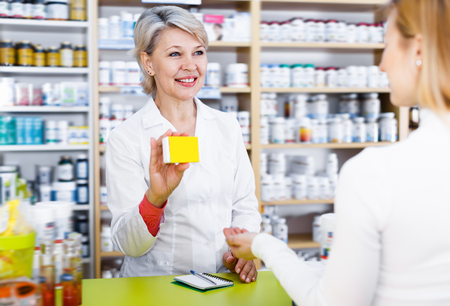 Cheerful woman recommending care products to customer in specialized shop