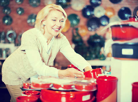 Mature happy woman chooses ceramic ware in the cookware section at hypermarket
