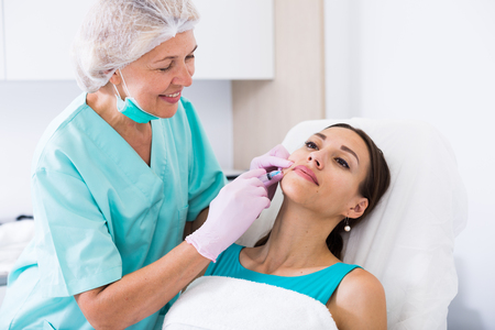 Female client receiving cosmetic injection from professional cosmetician Stock Photo