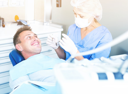 Professional dentist examining and performing treatment to young man