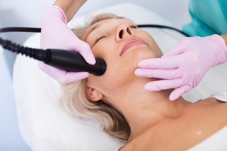 Senior woman face during cryolipolyse procedure in modern aesthetic clinic