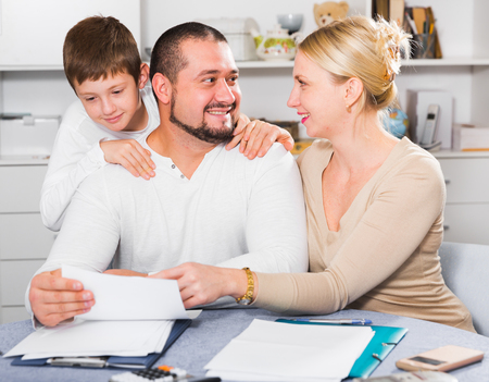 Portrait of happy parents with son looking at documents at home Stock Photo