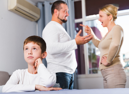 Upset tired son suffering from mom and dad arguing at home Stock Photo