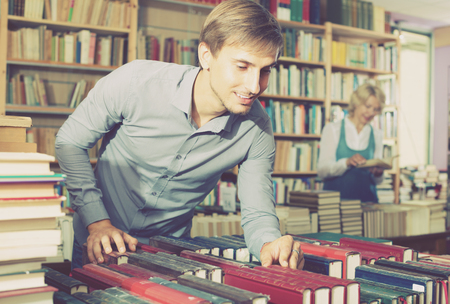 portrait of young  smiling man  in blue shirt standing among bookshelves and searching for book