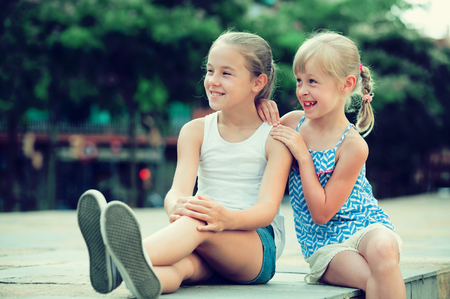 Two small happy sisters sitting outdoors, looking into distance
