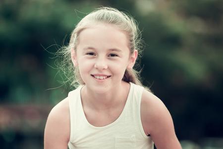Portrait of cute smiling little girl in summer park
