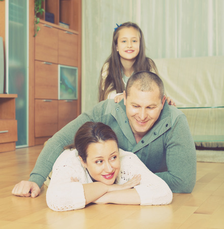 Happy smiling family of three on the floor at home. Focus on woman