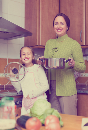 Smiling mother with little daughter cooking together at home kitchen. Focus on girl Banque d'images