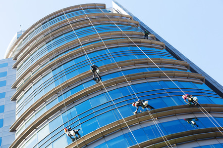 Group of industrial alpinists working on large windows of skyscraper Standard-Bild