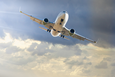 Large passenger airliner flying in sky with thundercloud Stock Photo