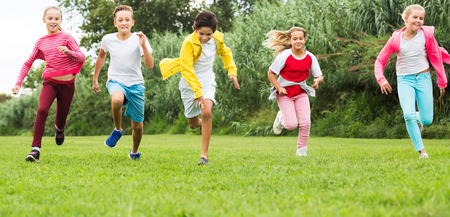 Smiling kids are jogging together in the park and having fun. Focus on girl