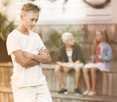 Upset boy offended after quarrel with playmates outside Stock Photo