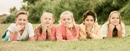 Company of five kids are posing lying on grass in the park Stock Photo