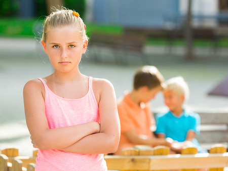 Portrait of girl 8-11 years old which is taking offense on her friends in the park. Stock Photo
