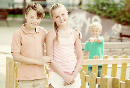 Smiling girl and boy are walking while their friend feeling aggrieved. Stock Photo