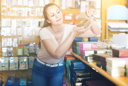 Positive housewife choosing  other gift boxes at shop