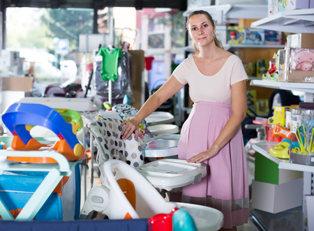 Pleasant pregnant female choosing chair for feeding baby from assortment at infant shop