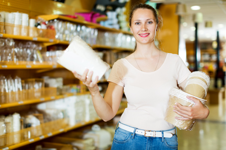 Positive woman demonstrates dishes, towels, napkins, disposable cups and tablecloth
