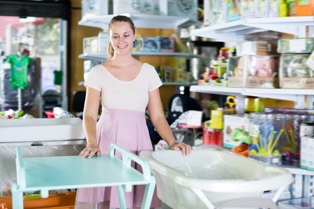 Positive pregnant woman choosing changing table for newborn in infant shop