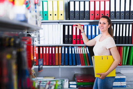 Portrait of positive woman looking products in stationery store