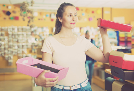 Laughing girl with gift boxes in her hands chooses accessories for gift in store Stock Photo