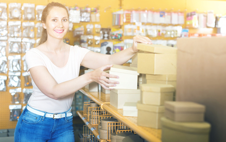 Smiling woman selects new boxes for gifts in the store