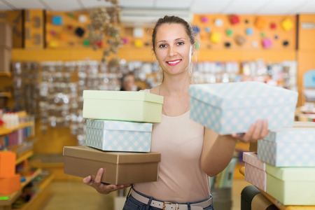 Young  female demonstrates multi colored container at shop Stock Photo
