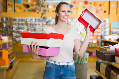 Positive girl with gift boxes in her hands chooses accessories for gift in store Stock Photo