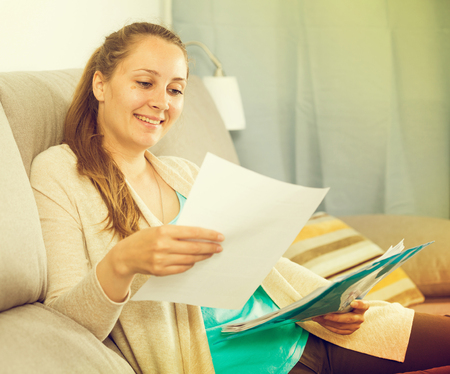 Smiling woman learner reading educational materials at home