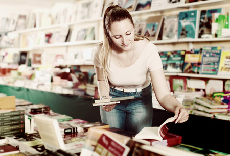 Portrait of smiling young woman selecting textbooks in book shop