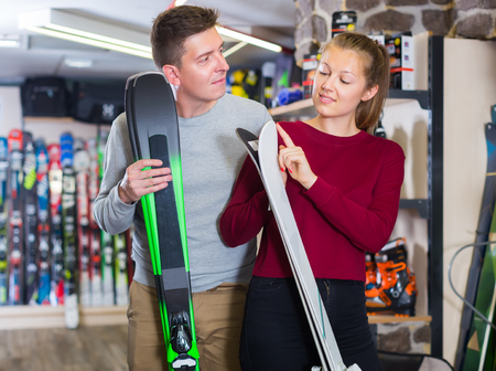 girl with guy are choosing ski in sport shop. Stock Photo
