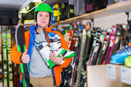 Portrait of happy spanish adult man in jacket and helmet who is demonstrating ski and boots in store.