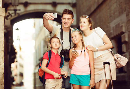 Nice family of tourists making selfie during travelling on European city