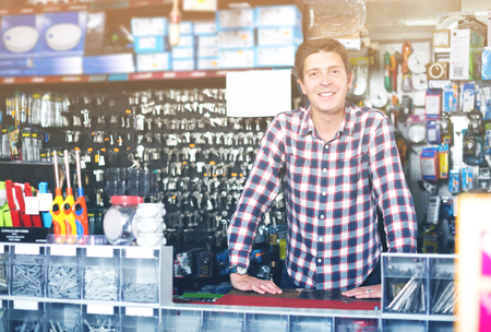 Smiling adult man standing near the counter and selling keys in hardware shop