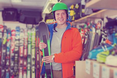 Portrait of customer male in helmet showing ski in sport shop Banque d'images