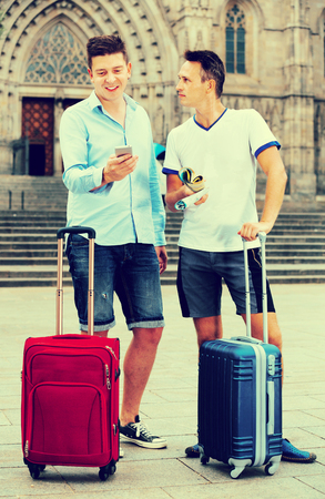 Happy male couple  with luggage using the map at smartphone