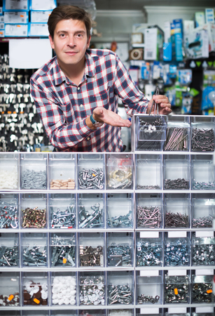 Portrait of adult smiling employee selling nuts, screw and fasteners in hardware store Stock Photo