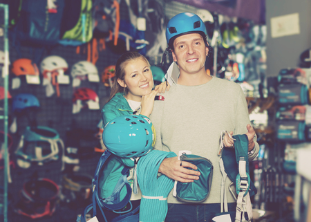 Portrait of young couple of customers with sports equipment in sports store