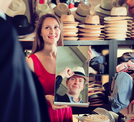 happy european woman holding mirror and showing customer his reflection in hats shop
