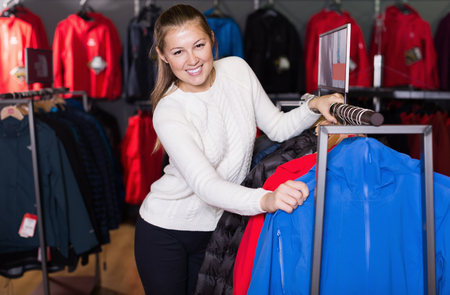 Young positive woman choosing sport clothes in sports store Foto de archivo