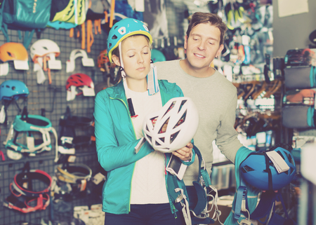 Girl and the guy choosing at a shop of sports equipment the mountaineering equipment. Focus on man Stock Photo