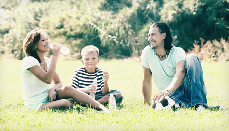 Happy parents with child drinking from plastic bottles in summer park Stock Photo