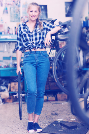 Young female is posing near bicycle in workshop. Stock Photo