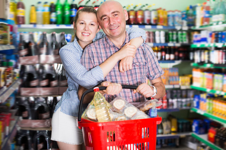 Cheerful woman and man with shopping basket in the supermarket