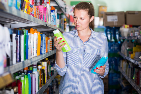 concentrated female holding shampoo and conditioner in the hand near the shelves at the shop  Banque d'images
