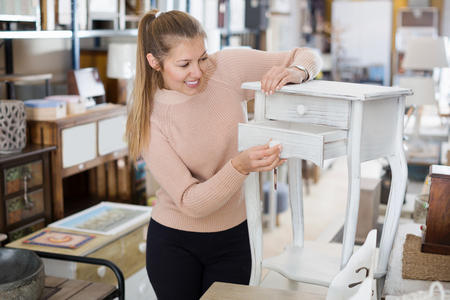 Positive woman customer choosing bedside in the furniture store